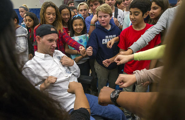Aaron Rubin, 31, who overdosed from prescription drugs and suffered catastrophic brain damage when he was 23, bumps fists with middle school students at the Corona Del Mar High School gym on Thursday. Rubin and his mother and father Sherrie and Michael Rubin talked to the students about the dangers of using drugs.