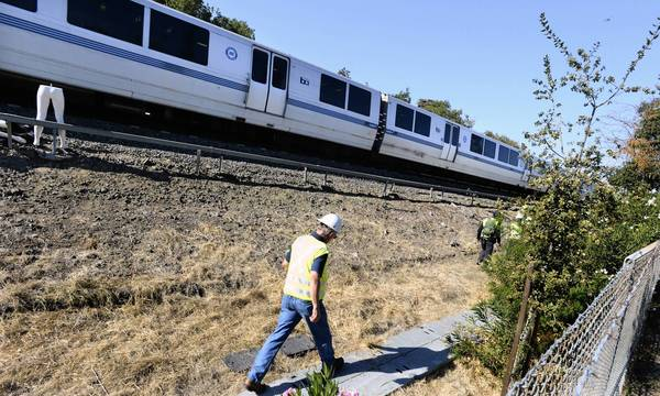 An investigator walk near tracks during a reenactment of an accident that killed two Bay Area Rapid Transit workers. BART is changing its safety rules for track workers.