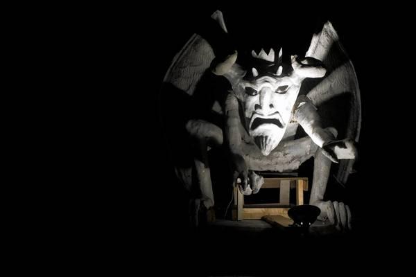 A gargoyle guards a scary scene at Halloween.
