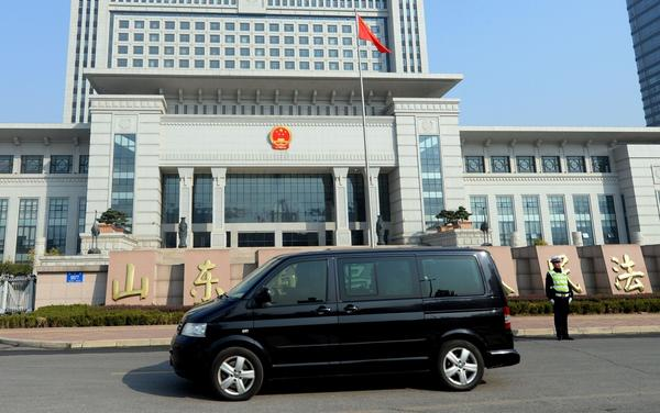 A vehicle believed to be ferrying once-powerful politician Bo Xilai arrives at the Shandong high court building in Jinan, in eastern China's Shandong province, on Friday.