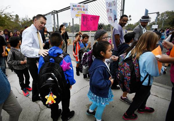 Los Angeles Unified School District Supt. John Deasy, left, talks to students on a walk to Calvert Charter Elementary School for Enriched Studies. Deasy has told some officials that he may resign soon.