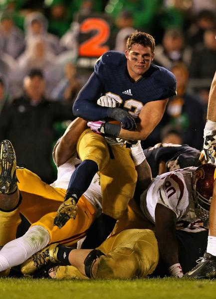 Notre Dame running back Cam McDaniel loses his helmet while being tackled by USC defenders last Saturday.