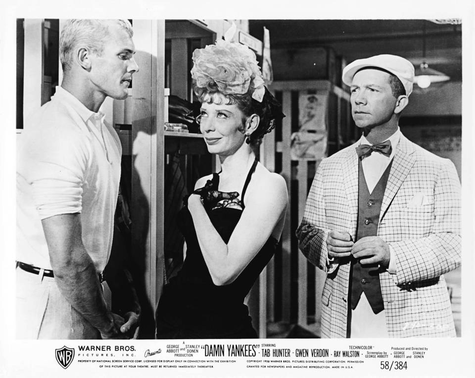 """Tab Hunter, Gwen Verdon, and Ray Walston standing together in the clubhouse in a scene from the 1958 film """"Damn Yankees."""""""