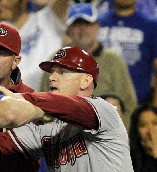 Los Angeles Dodgers hitting coach Mark McGwire is held back by Arizona Diamondbacks manager Kirk Gibson and third base coach Matt Williams, right, after Los Angeles starting pitcher Zack Greinke is hit by a pitch by Arizona's Ian Kennedy during a game last June.