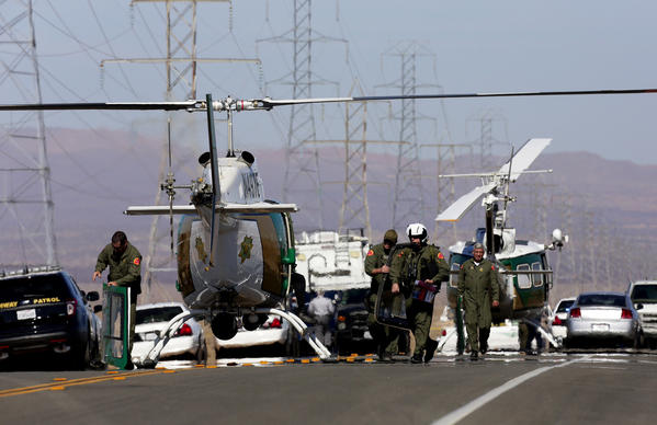 Law enforcement helicopters line Highway 395 between Kramer Junction and Ridgecrest after a suspect who allegedly opened fire on passersby during an hourlong police pursuit in Central California was killed and two people found with bullet wounds in the trunk of his vehicle were airlifted to an area hospital.