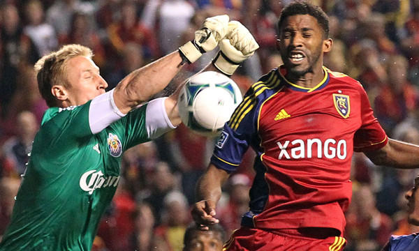 Chivas USA goalie Tim Melia, left, makes a save as Real Salt Lake midfielder Yordany Alvarez jumps during RSL's 2-1 victory Wednesday.