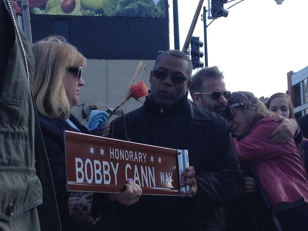 Ald. Walter Burnett (27th) gives a copy of the sign Honorary Bobby Cann Way to Maria Cann, Bobby's mother.