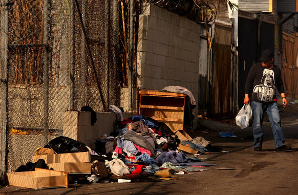 A pedestrian walks past furniture and clothing discarded in an alley in the Pico-Union neighborhood.