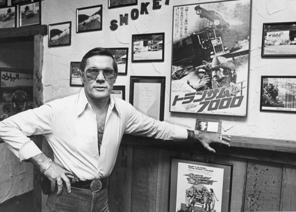"Hal Needham in 1980 with photos and posters from the movie ""Smokey and the Bandit,"" which he directed."