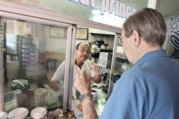 Donut Prince owner Mike Abdelghani helps longtime customer Glenn Brown with coffee and, of course, a donut on Monday, August 26, 2013.
