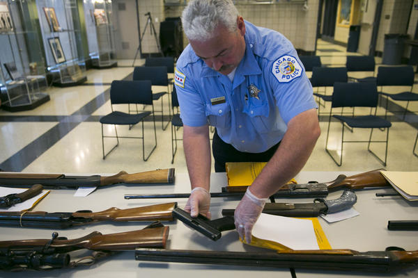 Chicago Police Officer John Cawley secures confiscated weapons on display Tuesday, Sept. 3, 2013 before returning them to an evidence locker at the Deering District Headquarters on the South Side, where Chicago Police Supt. Garry McCarthy had announced during an earlier news conference that police have seized more than 4,800 illegal firearms so far this year.