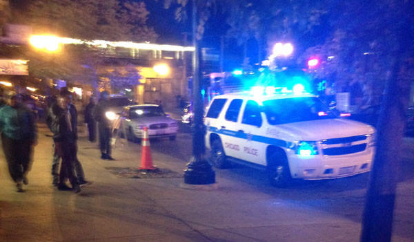 Police and bystanders at the scene of a shooting west of Broadway on Wilson Avenue Friday night.