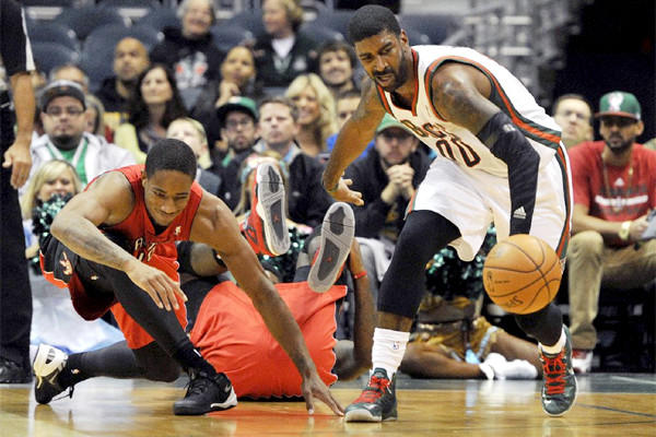 Toronto's DeMar DeRozan, left, slips as he and Milwaukee's O.J. Mayo, right, chase a loose ball during a preseason game at BMO Harris Bradley Center. The game was canceled because of safety concerns about the court in the first quarter.