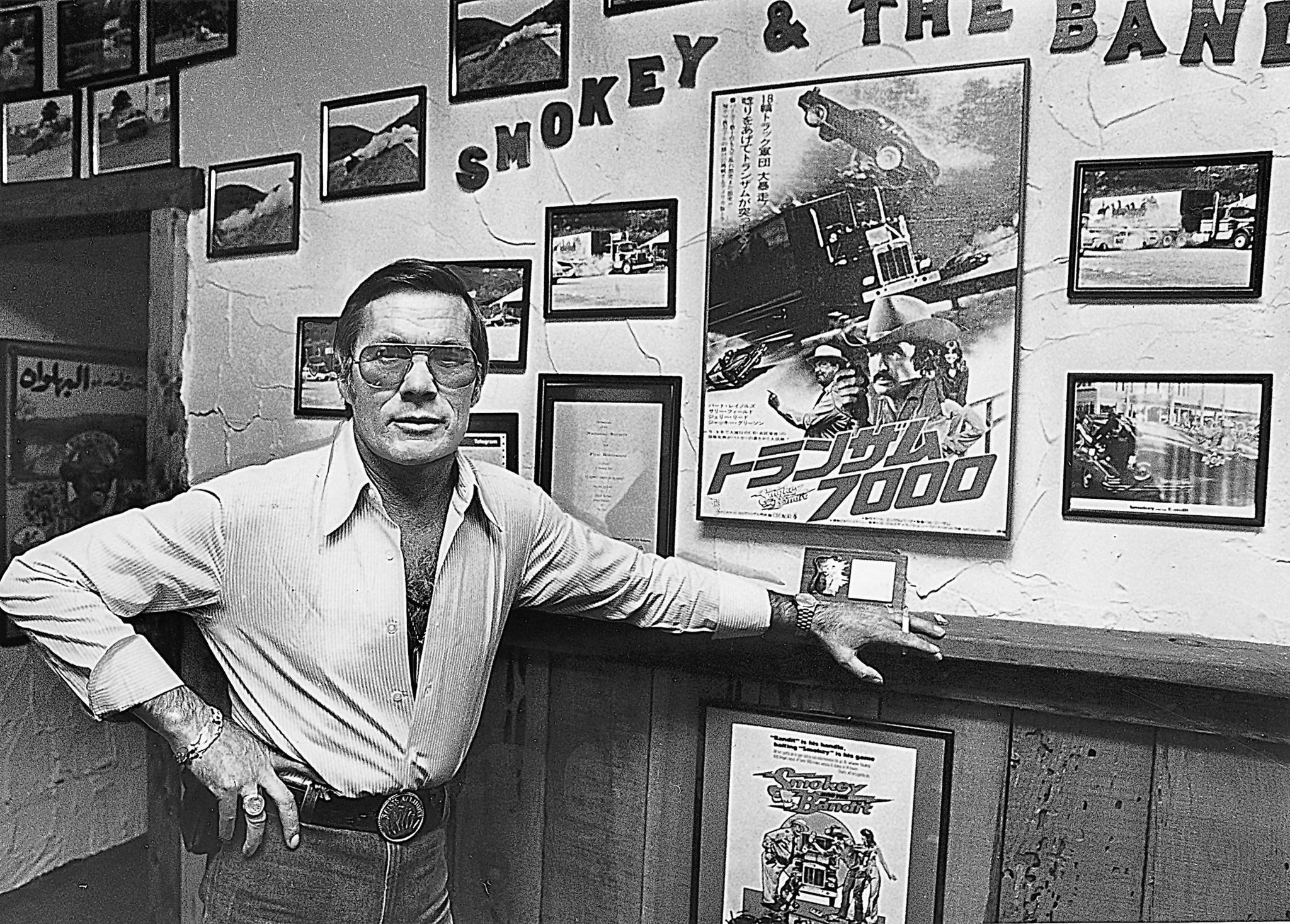 "Hal Needham poses with photos and posters from ""Smokey and the Bandit,"" one of the films he directed."