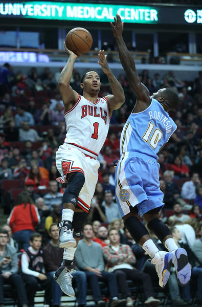 Derrick Rose aims for the basket against the defense of Nate Robinson.