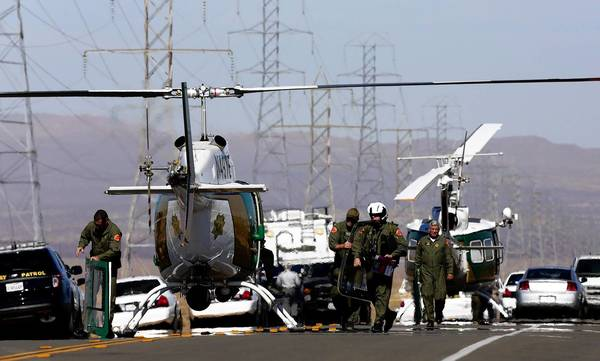 Helicopters and police vehicles block U.S. 395 in Central California south of Ridgecrest where officers killed a gunman after an hourlong chase. Two wounded people were found in the trunk of the fleeing car.