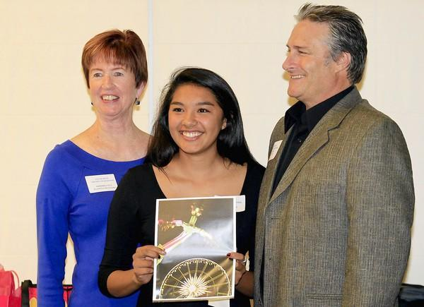 Costa Mesa High's Amy Roman, 17, smiles for a photo with Barbara Steck, left, Costa Mesa Library Foundation president, and John Clark, right, a contest judge and Senior Tech/Digital Photography teacher at Orange Coast College, after accepting her award during a ceremony at Orange Coast College on Wednesday. Roman was awarded an Honorable Mention in the 11th- and 12th-grade photography competition.