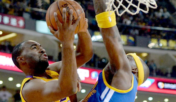 Marcus Landry is blocked by Jermaine O'Neal during a Lakers preseason exhibition against the Golden State Warriors in Beijing. Landry was waived by the team after Friday's 111-106 victory over the Utah Jazz.