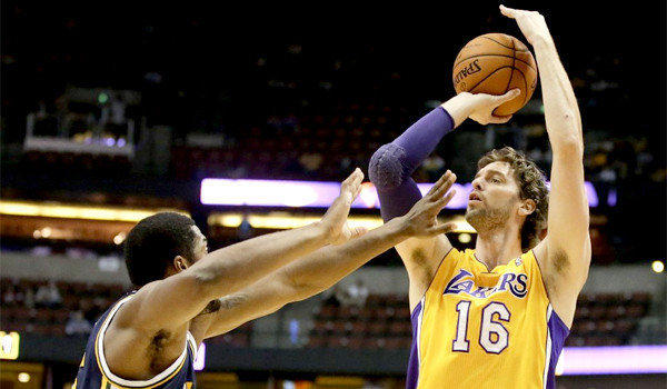 Pau Gasol shoots over Derrick Favors during the Lakers' 111-106 win over the Utah Jazz in a preseason exhibition game at the Honda Center.