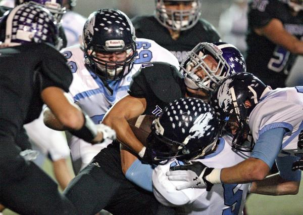 Hoover High's Kenneth Traquena can't get past the Crescenta Valley defense during a Pacific League game at Moyse Field on Friday. The Falcons won, 56-16. (Roger Wilson/Staff Photographer)