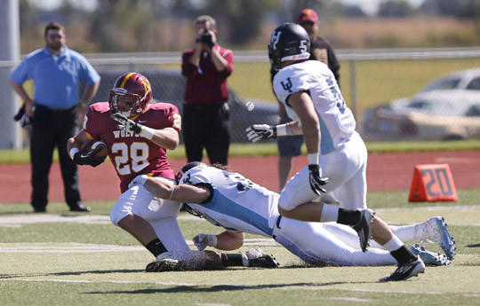 Northern State University's Cameron Pudwill, left, is tackled by Upper Iowa's Ethan Douglas as Jordan Andera (5) looks on during Saturday's game at Swisher Field. photo by john davis taken 9/21/2013