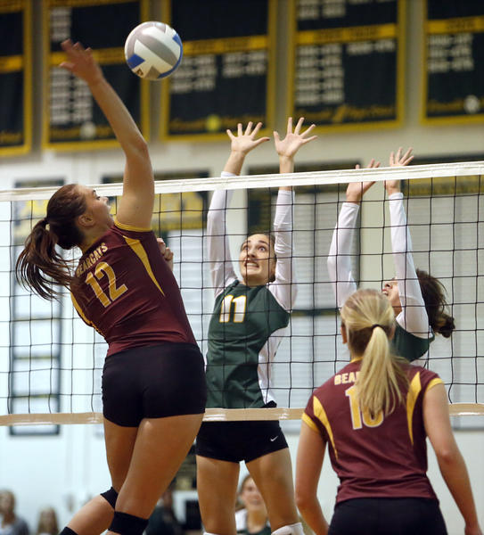 Webster's Breanna Bullert, left, reaches to hit the ball as Aberdeen Roncalli's Mariah Goetz (11) and Keary Spraw defend the net during Friday night's match at the Roncalli High School gym. In the foreground for Webster is Marisa Keller (10). photo by john davis taken 10/25/2013
