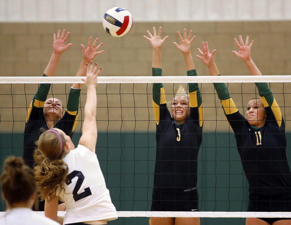 Presentation College's Mo Bunney, left, Karly Fuhrman, center and Megan Goedert, right, defend the net as Oak Hills Christian College's Megan Hogetvedt (2) hits the ball during Friday's match at the Strode Activity Center. photo by john davis taken 10/25/2013