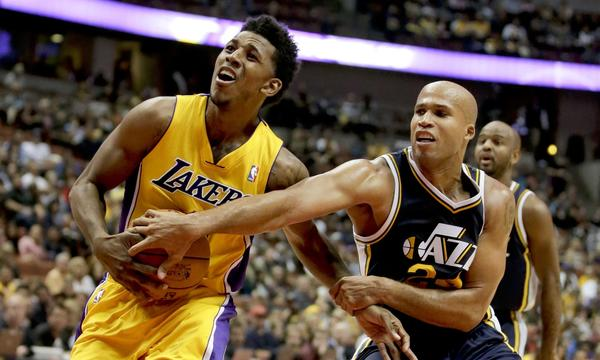 Lakers guard Nick Young, left, is fouled by Utah Jazz forward Richard Jefferson during the first half of the Lakers' 111-106 preseason win Friday at Honda Center.