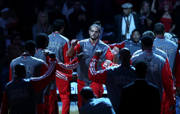 Joakim Noah is welcomed by his teammates as the starting lineups are announced before a preseason game.