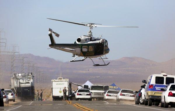 Law enforcement helicopters and police cruisers block Highway 395 between Kramer Junction and Ridgecrest after a suspect who opened fire on passersby during an hourlong police pursuit in Central California was killed and two people found with bullet wounds in the trunk of his vehicle were airlifted to an area hospital.