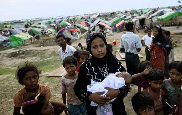 A woman with her newborn at a camp for displaced ethnic Rohingya people in Sittwe, Myanmar. About 140,000 Rohingya live in squalid displacement camps, where work is scarce and movement restricted by armed police.