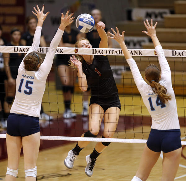 Northern State University's Kelsey Chambers, center, hits the ball past Upper Iowa's Jennifer Mundt, left and Alisha VanderWoude, right, during Saturday's match at Wachs Arena. photo by john davis taken 10/26/2013