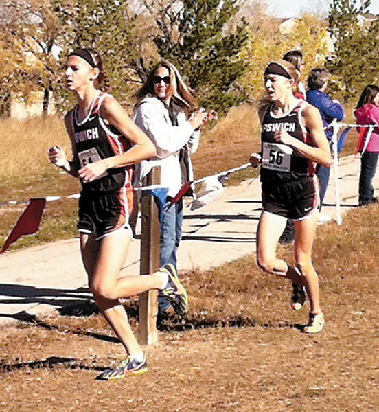 Macy Heinz of Ipswich leads teammate Tori Moore at the state cross country meet in Rapid City Saturday.