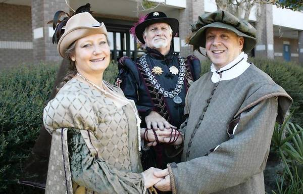 Renewing their vows in a handfasting ceremony are Wendy and Cary Usrey. Performing the ceremony at rear is Ron Michael.