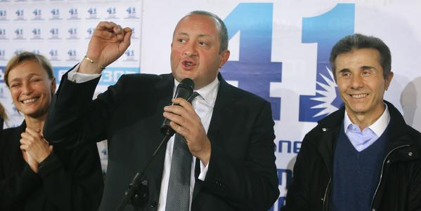 Georgian Prime Minister Bidzina Ivanishvili, right, and presidential candidate Giorgi Margvelashvili, center, greet supporters at the Georgian Dream coalition headquarters in Tbilisi.