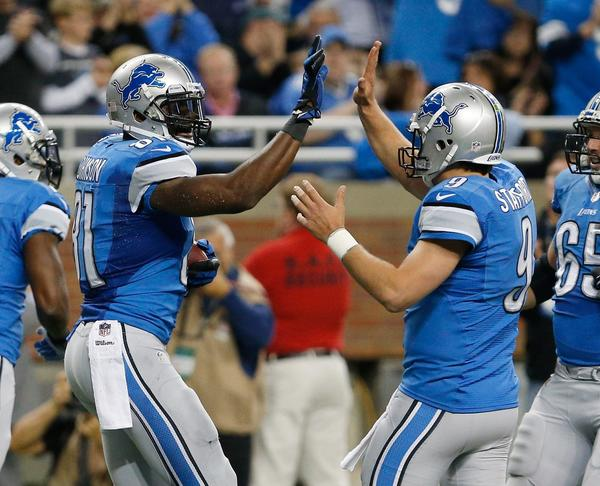 Calvin Johnson (leftO of the Detroit Lions celebrates a first quarter touchdown with Matthew Stafford while playing the Dallas Cowboys at Ford Field.