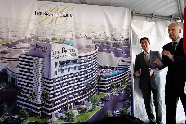 """Gov. Jerry Brown, right, and Hashem Minaiy, chief executive and managing general partner of the Bicycle Casino, unveil a mural of a 100-room hotel to be built at the card club in Bell Gardens. The project is """"another sign of the rebound of the California economy,"""" Brown says."""