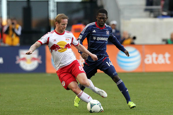 Red Bulls defender/midfielder David Carney and Patrick Nyarko fight for the ball during the first half.