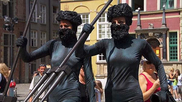 "In Detour A, Baseball wives Nicole (left) and Kim must dress and pose as a statue of Neptune on ""The Amazing Race."""