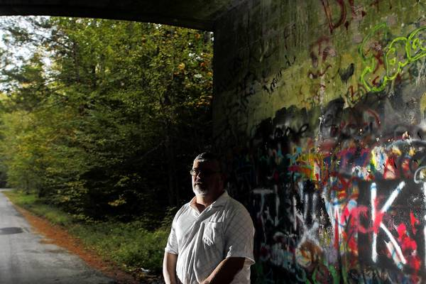 Frank Green, a retired York deputy sheriff and president of the York County Historical Association stands along Crawford Road Tuesday evening. Crawford Road has a history of being a haunted area.