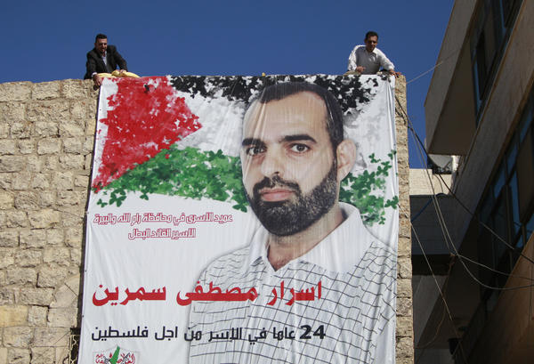 "Palestinian relatives of prisoner Israr Samreen, who has been jailed by Israel, hang a poster that reads, ""leader of prisoners in Ramallah, the heroic prisoner, Israr Mostafa Samreen, 24-year prisoner for Palestine."" Samreen is expected to be among the prisoners released by Israel this week."