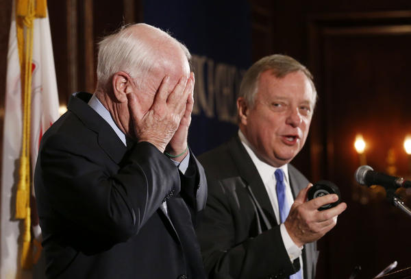 U.S. Senator Dick Durbin (D-IL) hands a Chicago Blackhawks hockey puck to Sen. John McCain (R-AZ) as they make a joint appearance at the City Club of Chicagos Public Policy Breakfast held at Maggiano's restaurant on Monday. Durbin was giving McCain a hard time about having a Stanley Cup winner in Illinois and no champion in Arizona. The two worked together to help craft the bipartisan Border Security, Economic Opportunity, and Immigration Modernization Act which was approved by the Senate on a bipartisan basis in June.