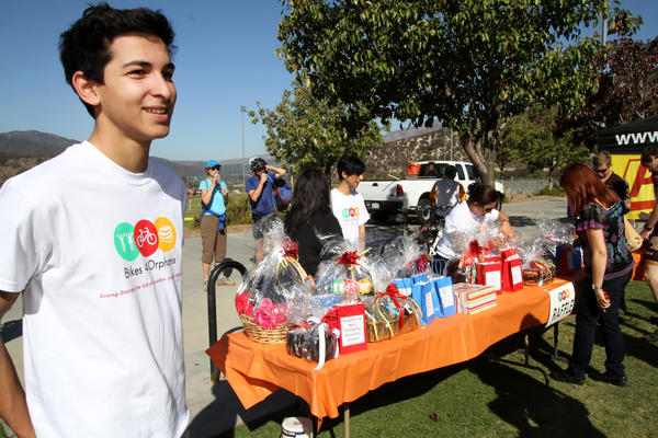 Sebouh Bazikian, who hosted a hike and bicycle event, looks over the prizes that were donated for his Bikes for Orphans event at the Glendale Sports Complex in Glendale on Saturday, Oct. 26, 2013.