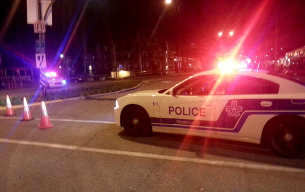 A Montreal police car blocks off a street near Pierre Trudeau International Airport after the discovery of a potential explosive device in the carry-on luggage of a 71-year-old man headed to Los Angeles.