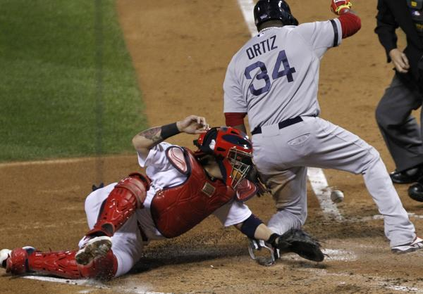 The Boston Red Sox's David Ortiz gets past the St. Louis Cardinals' Yadier Molina to score in Game 4 of the World Series.