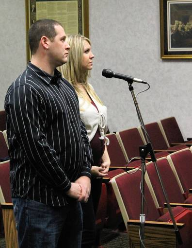 Michael and Ashley Moscato listen to discussion during a Zoning Board of Appeals public hearing on their request for a zoning variance to extend their garage.