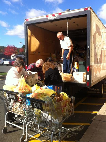 Volunteers load the Gifts of Love truck with food donations that were collected during a Give-A-Treat Get-A-Treat event.
