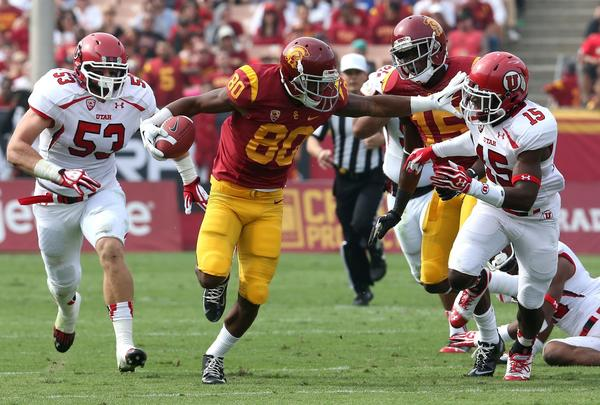 USC receiver De'Von Flournoy stiff-arms Utah safety Michael Walker on Saturday.