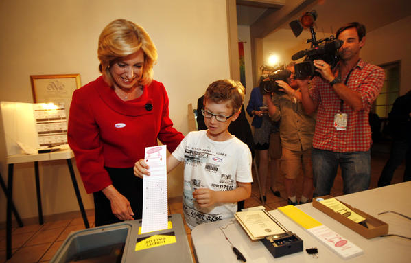 Then-L.A. mayoral candidate Wendy Greuel, left, watches as her son, 9-year-old Thomas Schramm, enters a voting ballot at the Unitarian Universalist Church in Studio City in May.