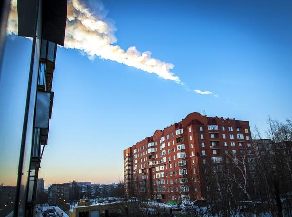 A meteorite trail seen above a residential apartment block in the Urals city of Chelyabinsk, Russia.
